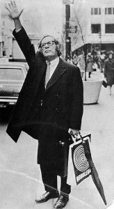 A man in conservative attire raises an open hand on the curb of a city street.