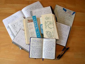 A pile of open notebooks with handwriting and drawings.