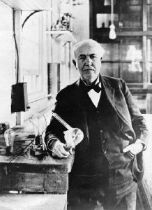 A white-haired man in coat and tie holding a lightbulb in a lab.
